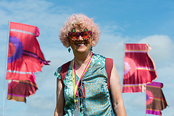 © Licensed to London News Pictures. 25/06/2015. Pilton, UK. Festival atmosphere at Glastonbury Festival 2015 on Thursday Day 2 of the festival.  An old woman with sparkly sunglasses and festival clothing.  This years headline acts include Kanye West, The Who and Florence and the Machine, the latter having been upgraded in the bill to replace original headline act Foo Fighters.   Photo credit: Richard Isaac/LNP