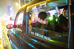 """© Licensed to London News Pictures . 22/12/2017. Manchester, UK. A man with his eyes closed leans against his arm in the window of a taxi on Deansgate . Revellers out in Manchester City Centre overnight during """" Mad Friday """" , named for being one of the busiest nights of the year for the emergency services in the UK . Photo credit: Joel Goodman/LNP"""