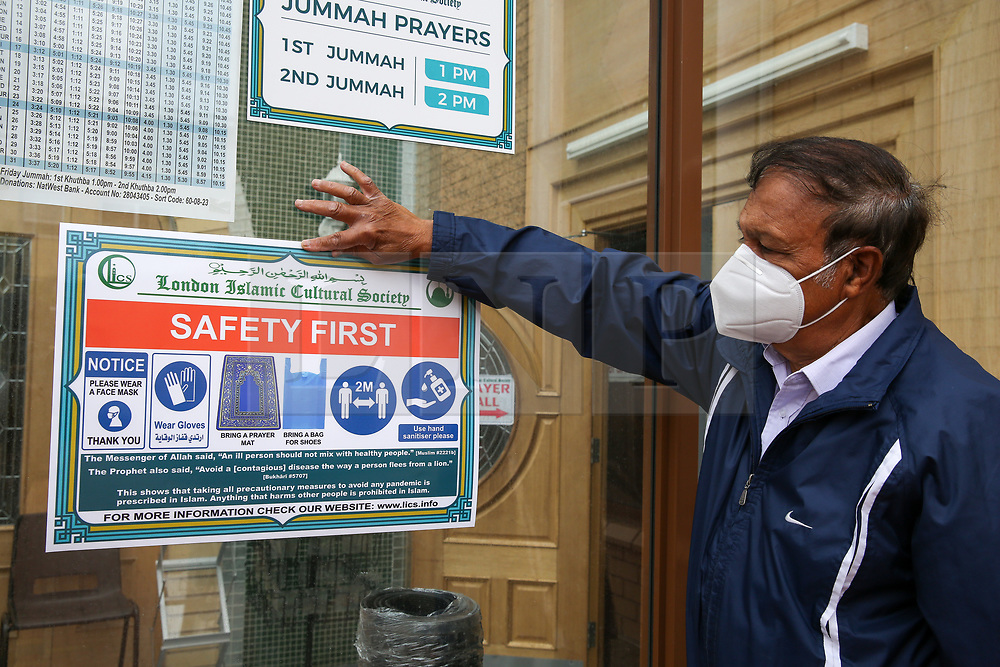 © Licensed to London News Pictures. 06/07/2020. London, UK. A member of staff displays 'SAFETY FIRST' sign at the entrance of the Mosque. Wightman Road Mosque, also known as London Islamic Cultural Society and Mosque, in north London, prepares to open after the COVID-19 lockdown, by placing a number of measures required by law for worshippers. The government announced that gatherings of more than 30 worshippers are allowed for acts of communal worship in churches, synagogues, mosques, temples and other places of worship. All worshippers attending Mosques will have to wear face coverings and bring their own prayer mat, Quran, and a reusable shoe bag. Photo credit: Dinendra Haria/LNP