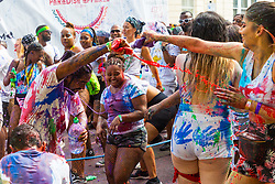 A paint fight erupts on Ladbroke Grove as day one, Children's Day, of the Notting Hill Carnival gets underway in London. London, August 25 2019.