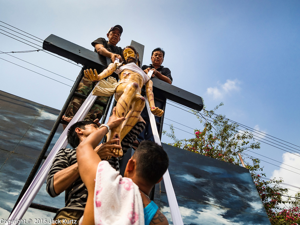 25 MARCH 2016 - BANGKOK, THAILAND: Men reenact the crucifixion during Good Friday observances at Santa Cruz Church in Bangkok. Santa Cruz was one of the first Catholic churches established in Bangkok. It was built in the late 1700s by Portuguese soldiers allied with King Taksin the Great in his battles against the Burmese who invaded Thailand (then Siam). There are about 300,000 Catholics in Thailand, in 10 dioceses with 436 parishes. Good Friday marks the day Jesus Christ was crucified by the Romans and is one of the most important days in Catholicism and Christianity.      PHOTO BY JACK KURTZ