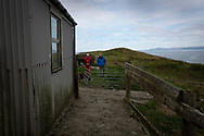 GP Dr David Binnie chatting to patient Walter Williams at his home at Kiloran Bay on the the Inner Hebridean island of Colonsay on Scotland's west coast.  The island is in the council area of Argyll and Bute and has an area of 4,074 hectares (15.7 sq mi). Aligned on a south-west to north-east axis, it measures 8 miles (13 km) in length and reaches 3 miles (4.8 km) at its widest point, in 2019 it had a permanent population of 136 adults and children.
