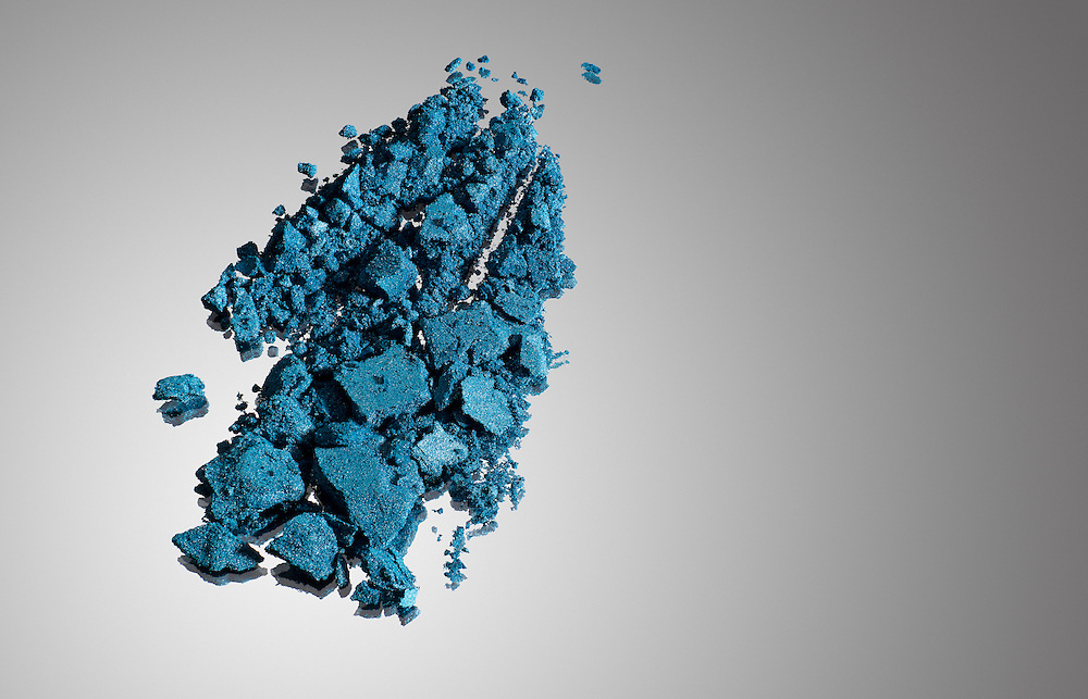 Macro of blue makeup powder on a gray gradient background.