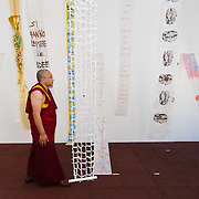 """VENICE, ITALY - JUNE 04:  A Tibetan Monk looks walks through works by several artisits at """"The Pavillion Tibet"""" a project by Ruggero Maggi on June 4, 2011 in Venice, Italy. The Venice Art Biennale will run from June 4 to November 27, 2011."""