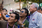 """15 JANUARY 2014 - BANGKOK, THAILAND: SUTHEP THAUGSUBAN, former Deputy Prime Minister of Thailand and leader of the Shutdown Bangkok anti-government protests, talks to supporters on Sukhumvit Road in Bangkok during a protest march. Tens of thousands of Thai anti-government protestors continued to block the streets of Bangkok Wednesday to shut down the Thai capitol. The protest, """"Shutdown Bangkok,"""" is expected to last at least a week. Shutdown Bangkok is organized by People's Democratic Reform Committee (PRDC). It's a continuation of protests that started in early November. There have been shootings almost every night at different protests sites around Bangkok. The malls in Bangkok are still open but many other businesses are closed and mass transit is swamped with both protestors and people who had to use mass transit because the roads were blocked.    PHOTO BY JACK KURTZ"""