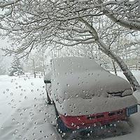 Viewed through a window,a van lies buried in snow during a storm near Bozeman, Montana.