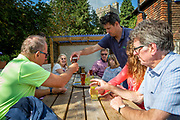 A group of people sit around a table and enjoy a drink outside the The Flying Horse Pub, Cage Land, Smarden, Kent, England, UK.  (photo by Andrew Aitchison / In pictures via Getty Images)