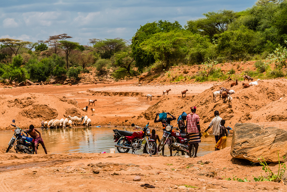 Men washing their motorcycles in a river bed, Omo Valley,  Southern Nations Nationalities and People's Region, Ethiopia.