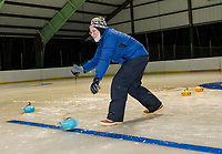 Dick Pease throws a stone for the blue team during the first night of curling with the Gilford Parks and Rec at the Arthur Tilton Ice Rink Thursday evening.  (Karen Bobotas/for the Laconia Daily Sun)
