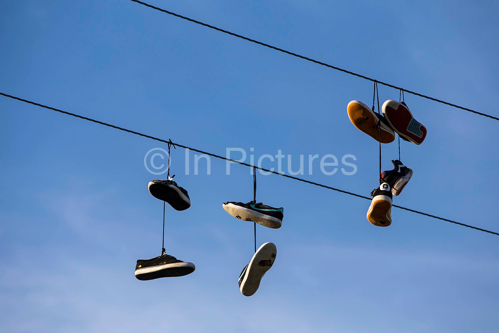 Pairs of shoes hanging on a wire. Wadebridge, Cornwall, UK. Shoe tossing, the act of using shoes as projectiles is a constituent of a number of folk sports and practices. The act of throwing a pair of shoes onto telephone wires, powerlines, or other raised wires.