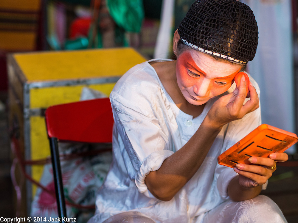 23 SEPTEMBER 2014 - BANGKOK, THAILAND:  A performer at the Chinese opera puts on her makeup on the first day of the Vegetarian Festival at the Chit Sia Ma Chinese shrine in Bangkok. The Vegetarian Festival is celebrated throughout Thailand. It is the Thai version of the The Nine Emperor Gods Festival, a nine-day Taoist celebration beginning on the eve of 9th lunar month of the Chinese calendar. During a period of nine days, those who are participating in the festival dress all in white and abstain from eating meat, poultry, seafood, and dairy products. Vendors and proprietors of restaurants indicate that vegetarian food is for sale by putting a yellow flag out with Thai characters for meatless written on it in red.    PHOTO BY JACK KURTZ