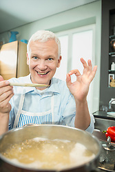Portrait of mature man preparing food in kitchen, smiling