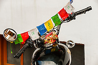 A motorcycle's handlebars covered with prayer flags, Leh, Ladakh, Jammu and Kashmir State, India.