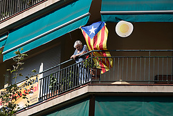 An old woman looks out from her balcony while tens of thousands of Catalans separatists march in protest in the centre of Barcelona during 'La Diada', the annual festival to mark National Day of Catalonia, demanding the independence of Catalonia.