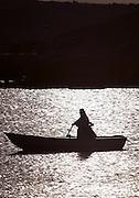 Native Uru woman rowing home at sunset, Lake Titicaka, Puno, Peru, South America