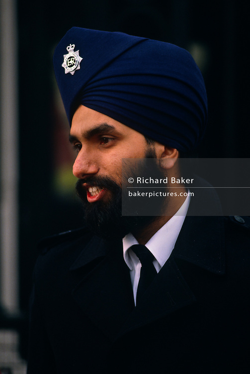 Wearing a turban according to the beliefs of the Sikh faith, a Metropolital police officer stands outside Buckingham Palace, London England UK. At a time when the 'Met' were recruiting members of ethnic minorities to demonstrate their tolerance of other commnities, this man is clearly a symbol of how Britain has changed, since the 1960s to a multi-cultural society