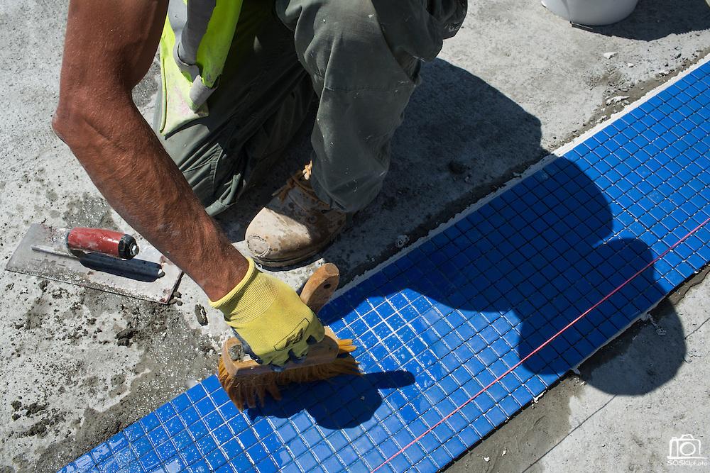 Enes Vukovic of Bosnia brushes water over lane marker tiles in the warming pool at Milpitas High School in Milpitas, California, on July 18, 2014. (Stan Olszewski/SOSKIphoto)