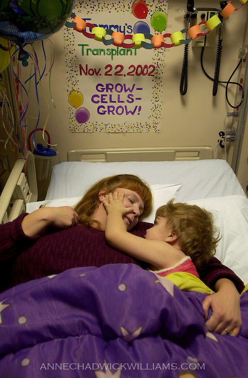 Alicia Bennett snuggles with Tommy in his Duke University Medical Center hospital bed three days after his umbilical cord blood transplant, which doctors hope will cure his Sanfilippo syndrome.  Alicia is living in Tommy's hospital room during his stay, which could be three months. November 25, 2002