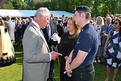 The Prince of Wales meets volunteer police cadet Harry Keane, who attended the aftermath of the Manchester Bombing, during a garden party at Buckingham Palace in London.