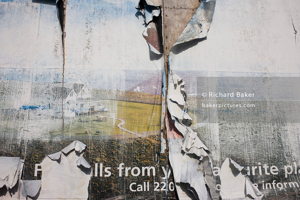 Dystopian landscape in peeling billboard advertising sheets near 2012 Olympic Park construction site in Stratford.