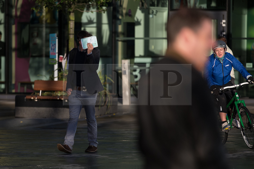 © Licensed to London News Pictures . 24/09/2014 . Media City , Salford , UK . A man shields his eyes with a book . Autumn sunshine and big reflected light off the surface of glass buildings at Salford's Media City this morning as commuters travel to work  . Photo credit : Joel Goodman/LNP