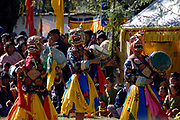 Dancers in painted animal masks and brightly coloured cloths dance and beat drums at the Paro festival. Paro, Bhutan. Druk Yul. 11 November 2007