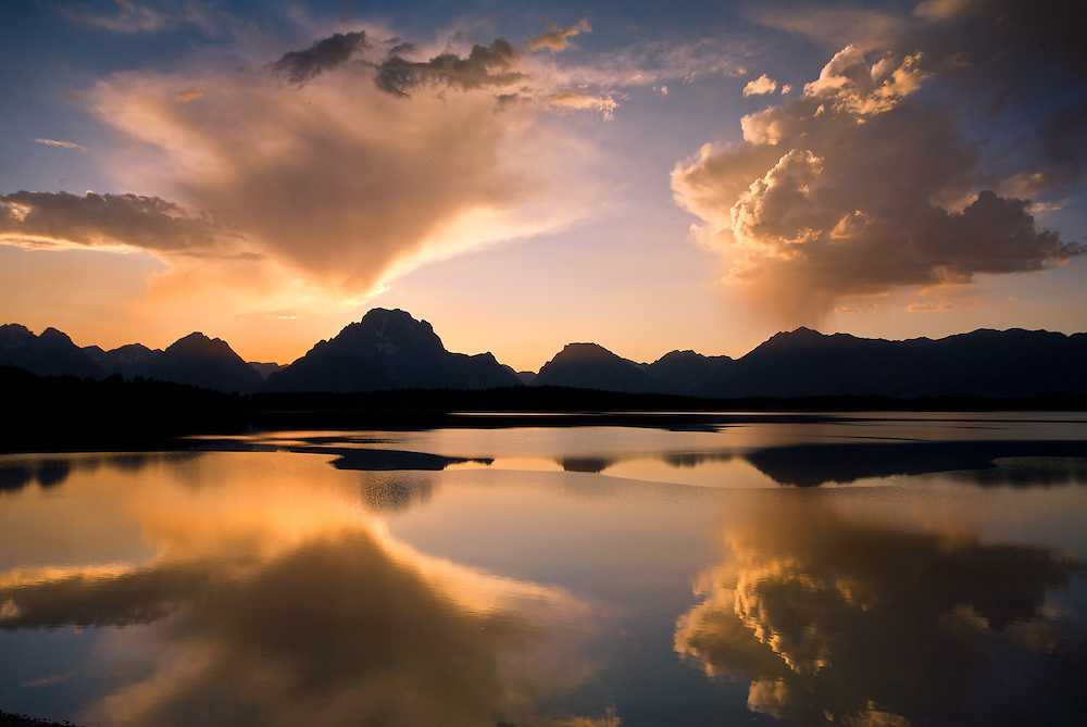 The setting sun colors clearing storm clouds over Jackson Lake, in Wyoming's Grand Teton National Park.