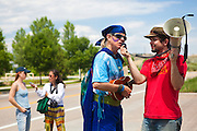 Activists are interviewed at a rally in front of the coal-fired Valmont Power Plant in Boulder, Colorado protesting its continued operation.