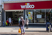 A member of staff sits by a health warning sign about social distancing and COVID-19 outside the entrance to Wilko the  the 10th of April 2020, in Folkestone, United Kingdom. All essential business's  including shops that sell food and cleaning products are still operating during the Corona virus outbreak now have strict health guidelines regarding COVID-19 for all people entering the premises regarding social distancing.  (photo by Andrew Aitchison / In pictures via Getty Images)