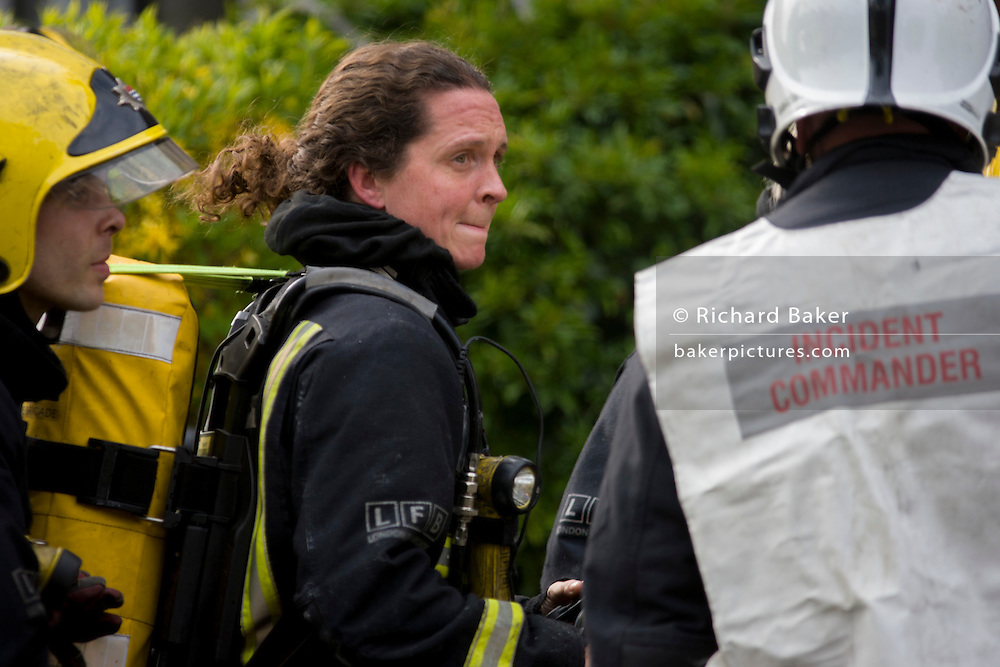 Female London Fire Brigade (LFB) firefighter attend a roof fire in Herne Hill, south London. s