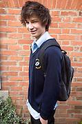 Model released portrait of teenage boy wearing navy blue school uniform, England, UK