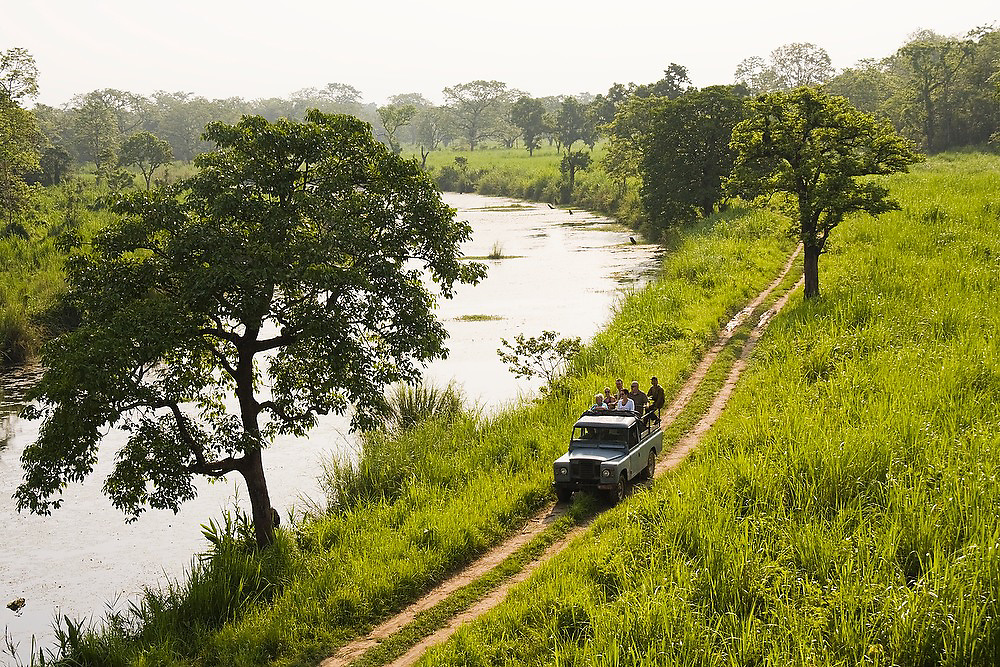 Tourists on a wildlife safari ride in the back of a jeep down a dirt road through Royal Chitwan National Park, Nepal.