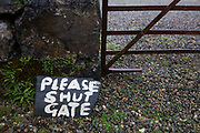 Please Shut the Gate sign lying on rain-soaked gravel at Kinlochspelve Church House by Thomas Telford on Isle of Mull, Scotland. Kinlochspelvie Church has only recently been available to let from Friday to Friday. Also available for Christmas and New Year. (http://canmore.rcahms.gov.uk/en/site/22381/details/mull+kinlochspelve+church/).