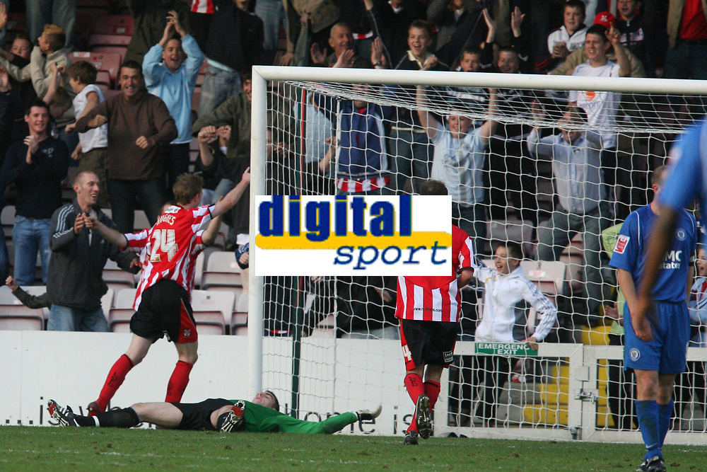 Photo: Pete Lorence.<br />Lincoln City v Rochdale United. Coca Cola League 2. 21/10/2006.<br />Lincoln's Jeff Hughes scores the 8th goal of the match as Matthew Gilkes lays stunned on the floor.