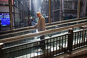 An elderly man on an escalator looks back in a ray of light. The escalator brings people down the steep hill in Mid-levels and up the rest of the day and night. 7 million people live on 1,104km square, making it Hong Kong the most vertical city in the world.