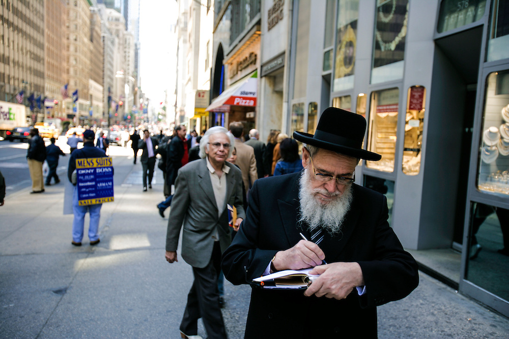 An orthodox jew takes notes on the street in New York.