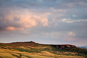 Over Owler Tor and Millstone Edge, lit by the evening sun, sit below colourful and dramatic clouds. An autumn sunset in the Derbyshire Peak District, England, UK.