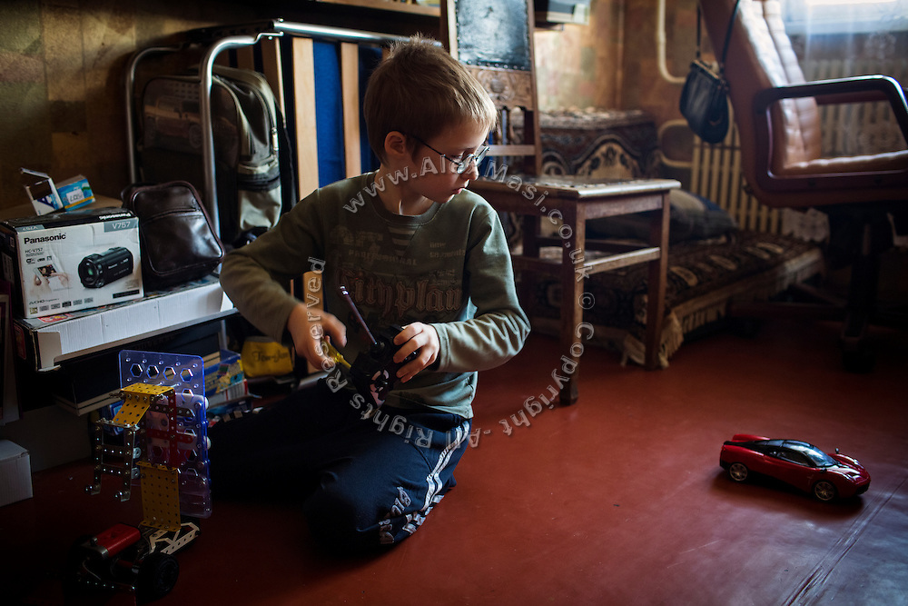 Yaroslav, 10, is playing with a remote-controlled car while sitting on the floor of the provisional home where he resides with his mother Olga, 36, as internally displaced persons. (IDPs) Yeroslav is taking part to the UNICEF-sponsored One Minute Junior project for internally displaced persons (IDPs), carried out by the local NGO 'Ukrainian Frontiers' in the city of Kharkiv, the country's second-largest, in the east. The conflict between Ukrainian army and Russia-backed separatists nearby, in the Donbass region, have left more than 10000 dead since April 2014, including over 1000 since the shaky Minsk II ceasefire came into effect in February 2015. The approximate number of people displaced by the conflict is 1.4 million as of August 2015. Yeroslav's mother, Olga, is also a participant to a different project of 'Ukrainian Frontiers', called 'Self-Employment', first as a beneficiary, and now as a paid hotline coordinator for people seeking jobs and formation courses.