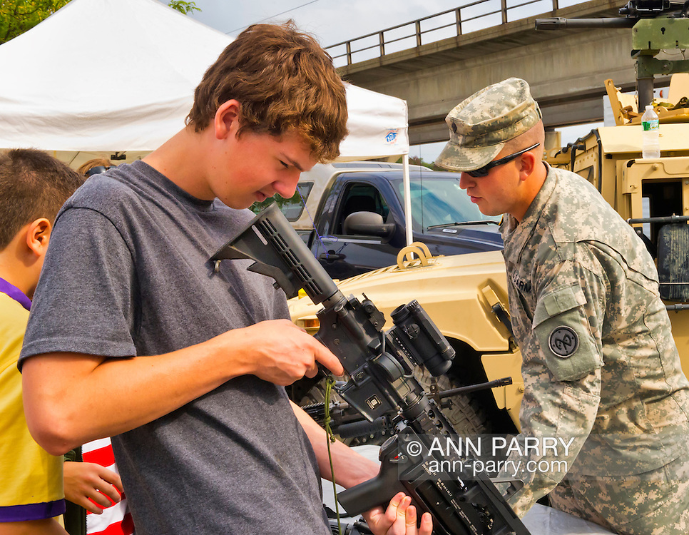Sept. 22, 2012 - Bellmore, New York U.S. - A teen boy looks through scope of machine gun at the U.S. Army area of Military Expo section at the 26th Annual Bellmore Family Street Festival. More people than the well over 120,000 who attended the Long Island fair last year were expected.