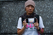 """A Japanese  woman holds a smart phone with the message """"Love Trumps Hate""""  at the  """"Enough is Enough"""" rally in Toranomon, Tokyo Japan, Tuesday August 15th 2017. Around 20 people gathered to take part in a global day of action demanding fairer policies in the United States that do not favour only the rich and do not remove human rights from ordinary people. A silent vigil was held for 30 minutes at 6pm so that the voices that could be heard after spoke louder. This is the closest it is possible to protest to the US embassy in Tokyo."""