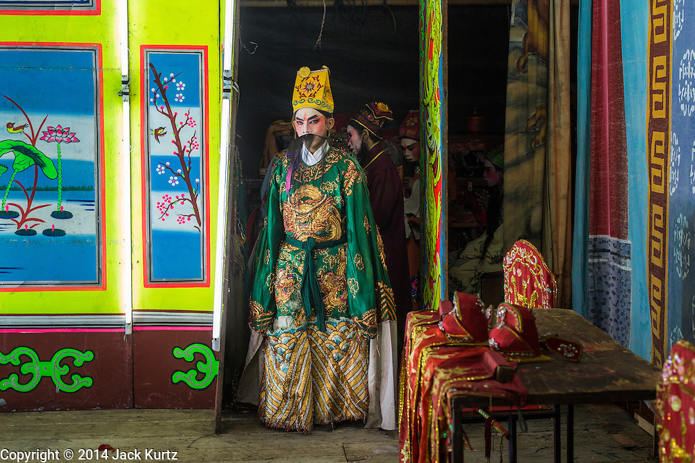 "25 JANUARY 2014 - BANG LUANG, NAKHON PATHOM, THAILAND: Performers with the Sing Tong Teochew opera troupe take the stage during a show in a Chinese shrine in the town of Bang Luang, Nakhon Pathom, Thailand. The Sing Tong Teochew opera troupe has been together for 60 years and travels through central Thailand and Bangkok performing for mostly ethnic Chinese audiences. Chinese opera was once very popular in Thailand, where it is called ""Ngiew."" It is usually performed in the Teochew language. Millions of Chinese emigrated to Thailand (then Siam) in the 18th and 19th centuries and brought their cultural practices with them. Recently the popularity of ngiew has faded as people turn to performances of opera on DVD or movies. There are still as many 30 Chinese opera troupes left in Bangkok and its environs. They are especially busy during Chinese New Year when travel from Chinese temple to Chinese temple performing on stages they put up in streets near the temple, sometimes sleeping on hammocks they sling under their stage.     PHOTO BY JACK KURTZ"