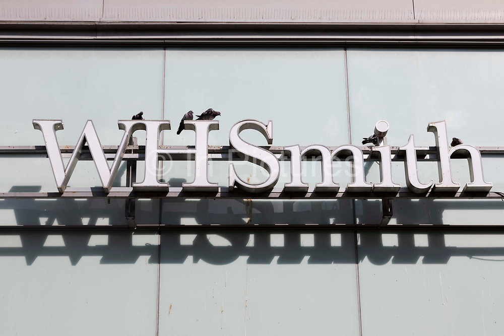 A sign for British retail chain WH Smith, also known as WHS or Smiths, with pigeons sat atop it on 26th August, 2021 in Manchester, United Kingdom. WH Smith is a 229-year-old British retail chain with shops in high streets, transport hubs, hospitals, and service stations internationally.