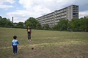 An asian man flying a kite with young child in Burgess Park on 31st July 2015 in South London, United Kingdom. On the horizon is the Aylesbury Estate, a large housing estate located in Walworth, South East London. It contains 2,704 dwellings and was built between 1963 and 1977. The whole estate is currently undergoing a major redevelopment with most of the dwellings are derelict.