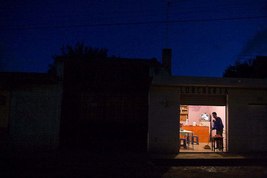 A man sweeps his home and small restaurant as night falls in Paracho, Michoacan state, Mexico.