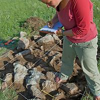 Smithsonian Museum archaeologist  Christina Leece studies a 2700+ year-old khirigsur burial mound at Ulaan Tolgoi site near Lake Erkhel & Muren, Mongolia.
