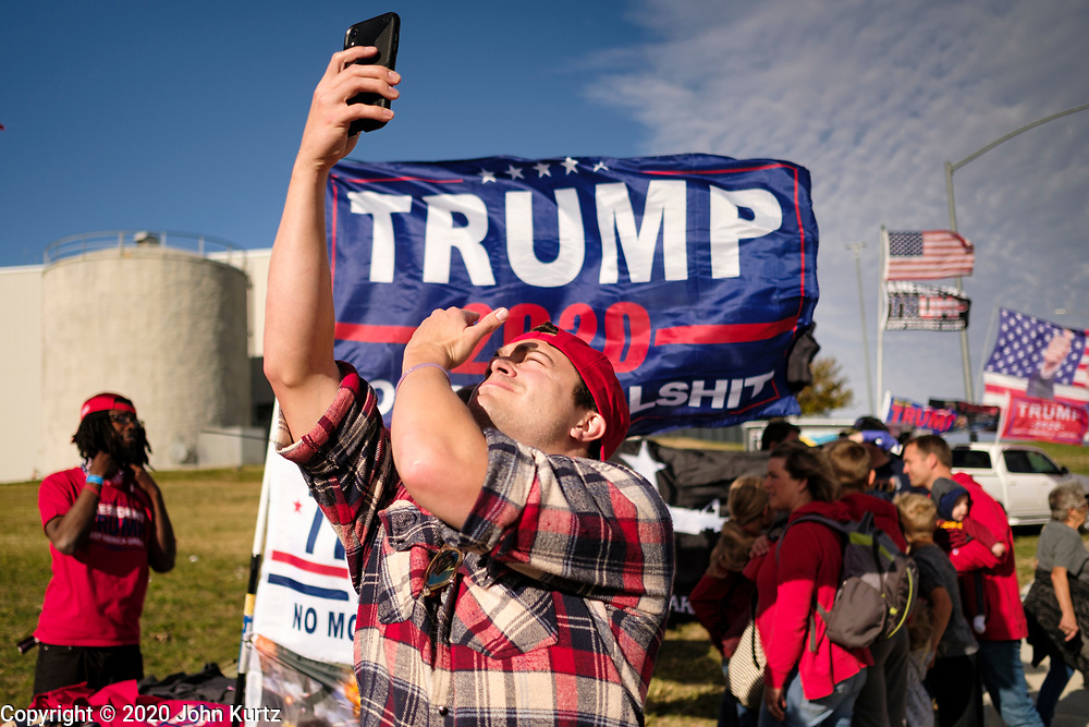 14 OCTOBER 2020 - DES MOINES, IOWA: AA man takes a selfie of himself in line for the Donald Trump reelection campaign rally. About10,000 people were expected at the Des Moines International Airport for a campaign rally supporting the reelection of President Donald Trump. Trump spoke at the rally, despite testing positive for COVID-19 less than three weeks ago. The rally did not meet the CDC guidelines for a safe gathering in the time of Coronavirus and violated Iowa's health emergency declarations barring gatherings of more than 25 people. This week Iowa exceeded 101,000 cases of COVID-19 and a surge in hospitalizations for COVID-19.       PHOTO BY JACK KURTZ