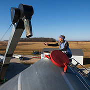 Jennifer Swope sits on top of a seed storage bin while guiding a seed elevator before transferring soybean seeds from a truck at LG Seeds in Hope, Indiana. LG Seeds supplies seed to customers to five surrounding counties. Nathan Lambrecht/Journal Communications