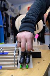 Teenage boy playing finger roller skates on a model ramp; North East England,