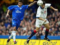 Photograph: Scott Heavey.<br /> Chelsea v Portsmouth. FA Barclaycard Premiership. 28/12/2003.<br /> Adrian Mutu is beaten in  the air by Dejan Stefanovic