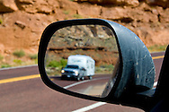 Vehicle and camper trailer in rear view mirror along scenic byway 9 near Springdale and Zion National Park, Utah